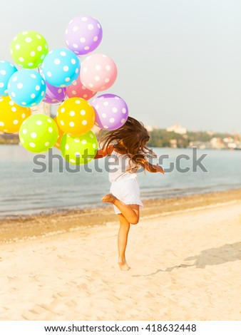 Happy little girl playing with balloons at the beach