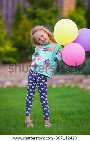 Happy little girl playing with balloons outdoors