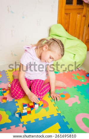 Happy little girl playing with blocks in the room - stock photo