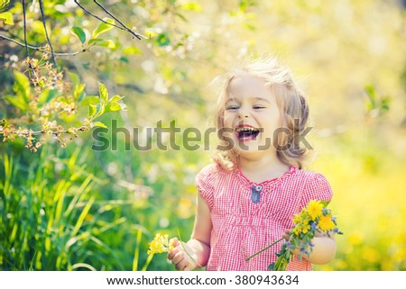 Happy little girl playing with bouquet in sunny park - stock photo