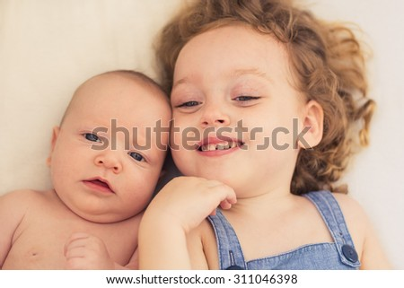 Happy little girl playing with her newborn brother - stock photo