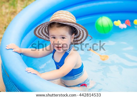 Happy little girl playing with rubber toys in the inflatable pool