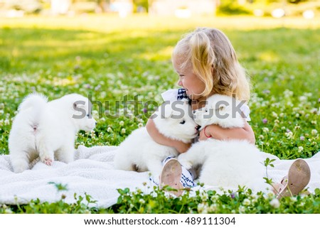 happy little girl playing with Samoyed puppy in the summer garden on the green grass
