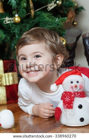 Happy little girl playing with toys near the Christmas tree
