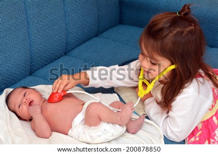 Happy little girl plays pretend to be a midwife or a doctor, checking the heart rate of her newborn baby sister. - stock photo