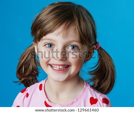 happy little girl portrait and blue background - stock photo