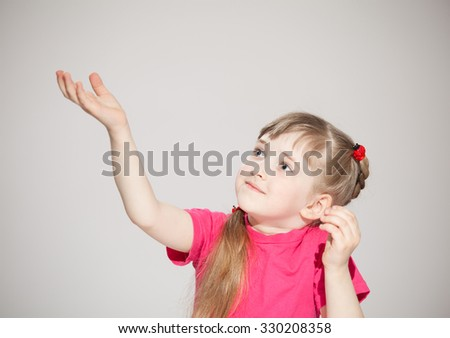 Happy little girl reaching out her palm and catching something, neutral background - stock photo