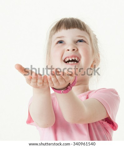 Happy little girl reaching out her palms and catching something, white background - stock photo