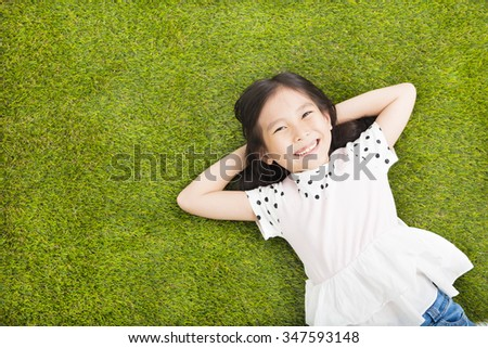 happy Little  girl resting on the grass - stock photo