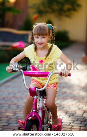 happy little girl riding a bicycle - stock photo