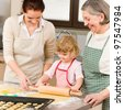 Happy little girl rolling out dough with mum and grandmother - stock photo