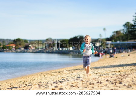 Happy little girl running along the beach on a cool summer day in Australia - stock photo