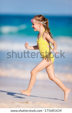 Happy little girl running and jumping at a beach - stock photo