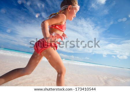 Happy little girl running and jumping at shallow water - stock photo