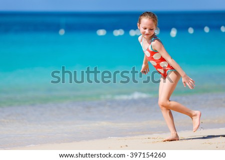 Happy little girl running and splashing at shallow water at beach having a lot of fun on summer vacation