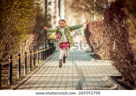 happy little girl running home from school - stock photo