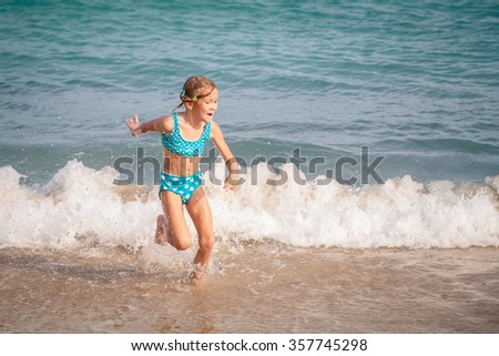 Happy little girl  running on the beach at the day time - stock photo