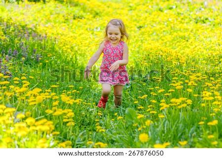 Happy little girl running on the dandelion field - stock photo