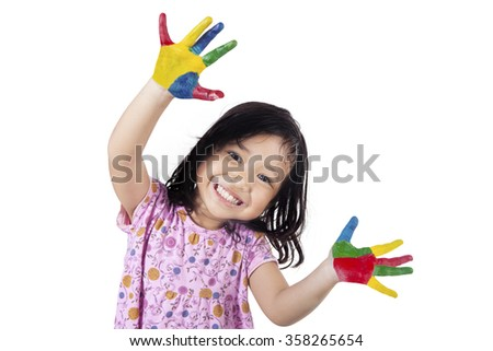 Happy little girl showing her hands painted in colorful paints, isolated on white background - stock photo