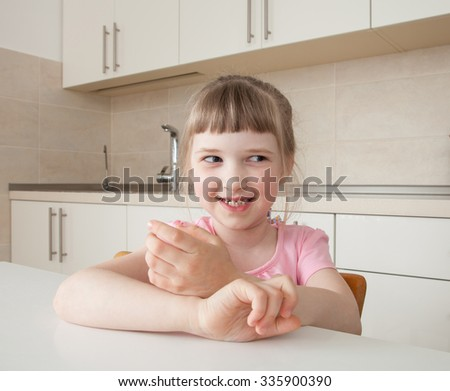 Happy little girl sitting at table at the kitchen - stock photo