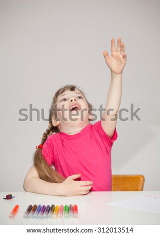Happy little girl sitting at the table and reaching out her hand and catching something, neutral background - stock photo