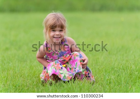 Happy little girl sitting in the grass - stock photo
