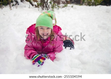 Happy little girl sitting in the snow making a snow ball (after snowfall in Jerusalem, 2015) - stock photo