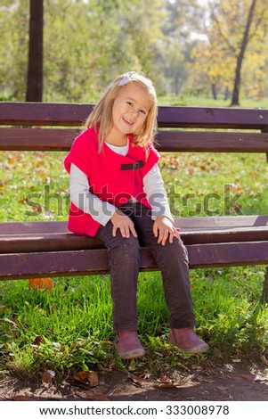 Happy little girl sitting on bench girl in the park. Autumn season.