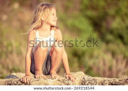 Happy Little girl  sitting on the beach at the day time - stock photo
