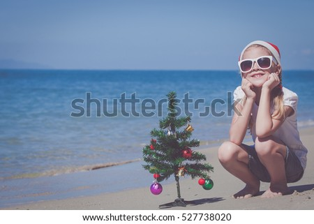 Happy little girl sitting on the beach at the day time. Concept of Happy New Year.