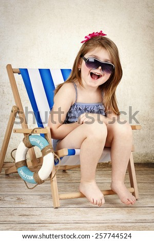 Happy little girl sitting on the deckchair, laughing and wearing sunglasses - stock photo