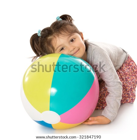 Happy little girl sitting on the floor with his head resting on a large inflatable striped ball-Isolated on white background - stock photo