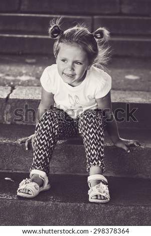 happy little girl sitting on the stairs - stock photo