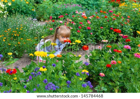 Happy little girl smelling the flower on the flower lawn - stock photo