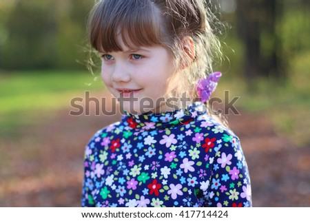Happy little girl smiles in sunny green park, shallow dof, close up - stock photo
