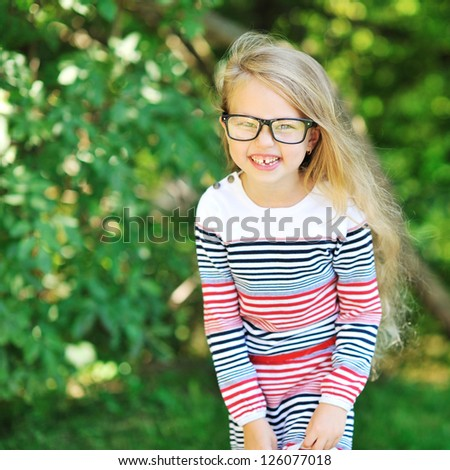 Happy little girl smiling in a park - stock photo