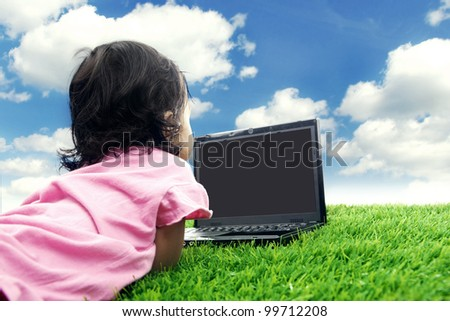 Happy little girl smiling on the laptop computer. Shot in meadow under clear sky