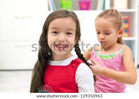 Happy little girl smiling while her girlfriend braiding plait