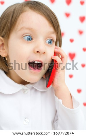 Happy little girl speaking by cell phone - stock photo
