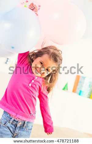 happy little girl surrounded by balloons