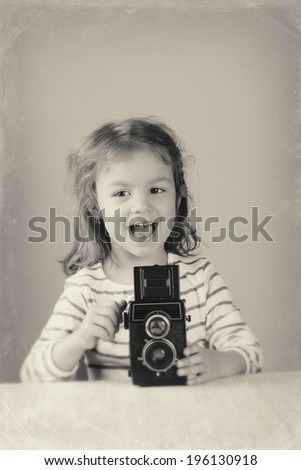 Happy little girl taking pictures with a vintage film lomography camera. Made in USSR. Black and White photography.  - stock photo