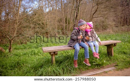 Happy little girl talking to the ear of a cute boy while eating muffins with chocolate chips sitting on a wooden bench in the park - stock photo