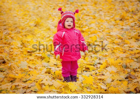 Happy little girl throws the autumn leaves in the air. happy child having fun on the playground - stock photo