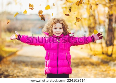 Happy little girl throws the autumn leaves in the air. Instagram filter. - stock photo