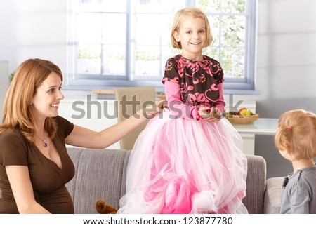 Happy little girl trying on princess outfit with pregnant mother and little sister. - stock photo