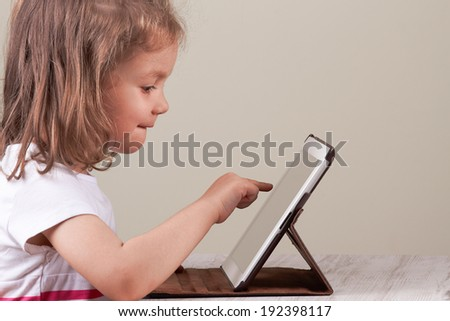 Happy little girl using tablet computer