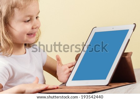 Happy little girl using tablet computer  - stock photo