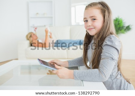 Happy little girl using tablet while mother is reading the newspaper on the couch - stock photo