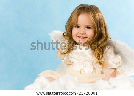 Happy little girl wearing angel dress sitting on white cloud and smiling - stock photo