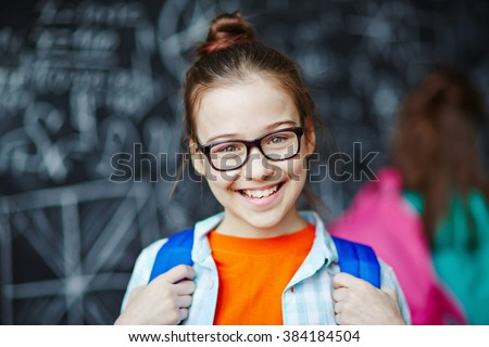 Happy little girl wearing glasses looking at camera - stock photo